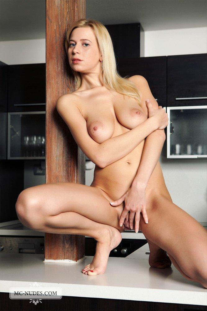 Титястая модель со свелыми волосами Anastasia Devine обнажает свои широко расставленные ножки на кухне