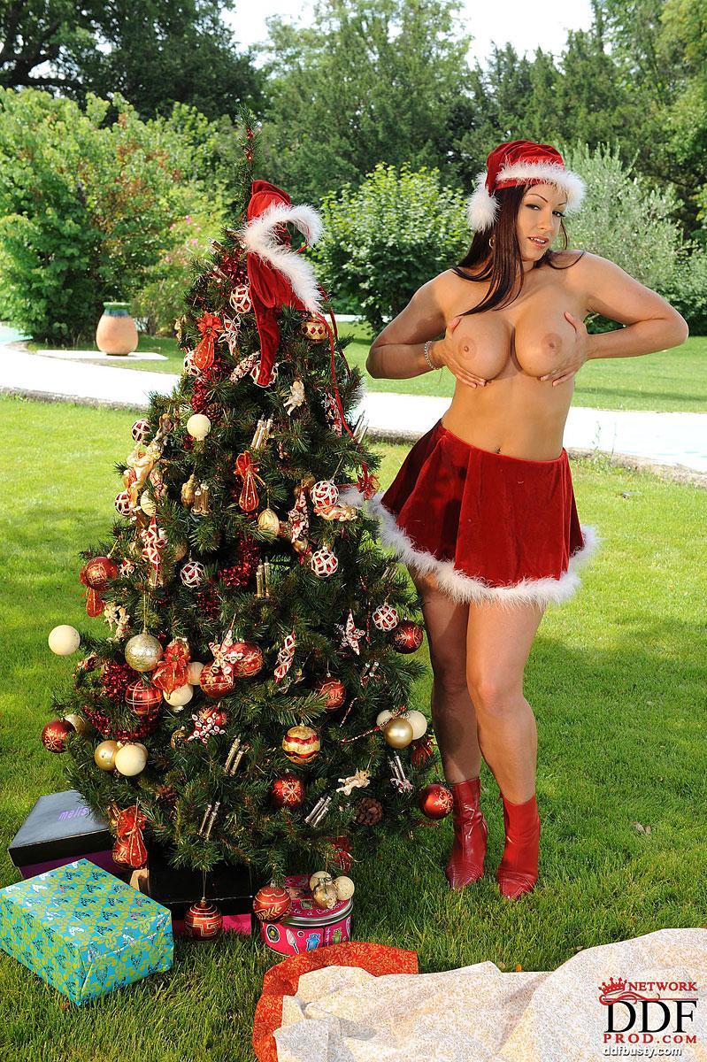 Брюнеточка с огромными грудями в костюме Санты - Aria Giovanni, возбужденно делает селфи и стаскивает тонги у елки