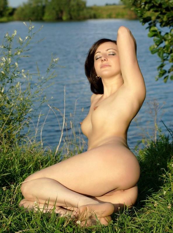 Тридцатилетняя модель с темными волосами обнаженная на озере