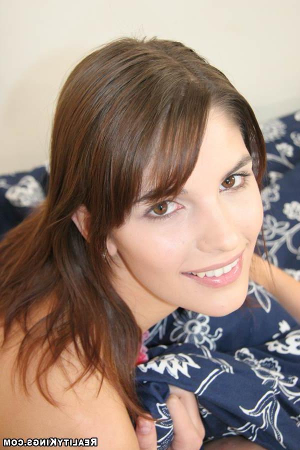 В ванной комнате модель с темными волосами расслабилась по крупной