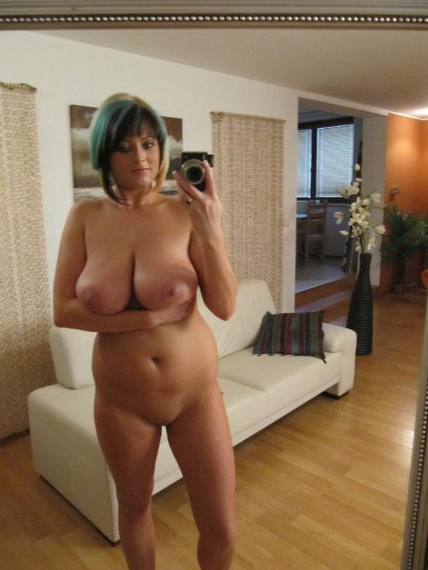 Домохозяйка с большими натуральными сиськами выставляет напоказ стриптиз перед зеркалом