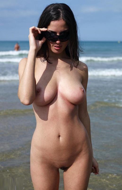 Брюнетка с 3 размером дойки позирует на нудистском пляже
