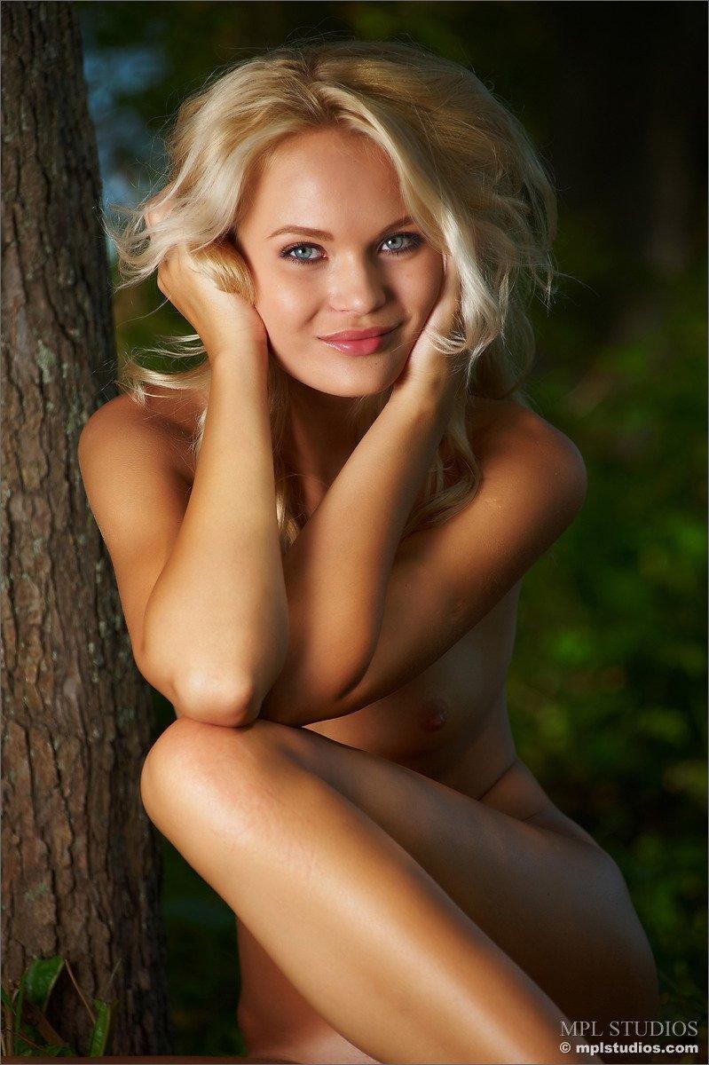 Хорошенькая модель со свелыми волосами сливается с природой и показывает своё красивое тело прямо недалеко от пейзажа