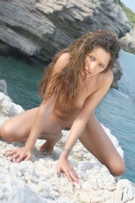 Возрастная туристка бродит в голом виде на скалистом берегу моря