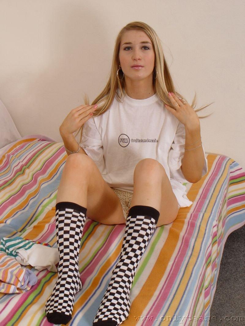 Возбужденная няшка в трусах Katie Onlytease обнажает свои любимые носочки на кроватке