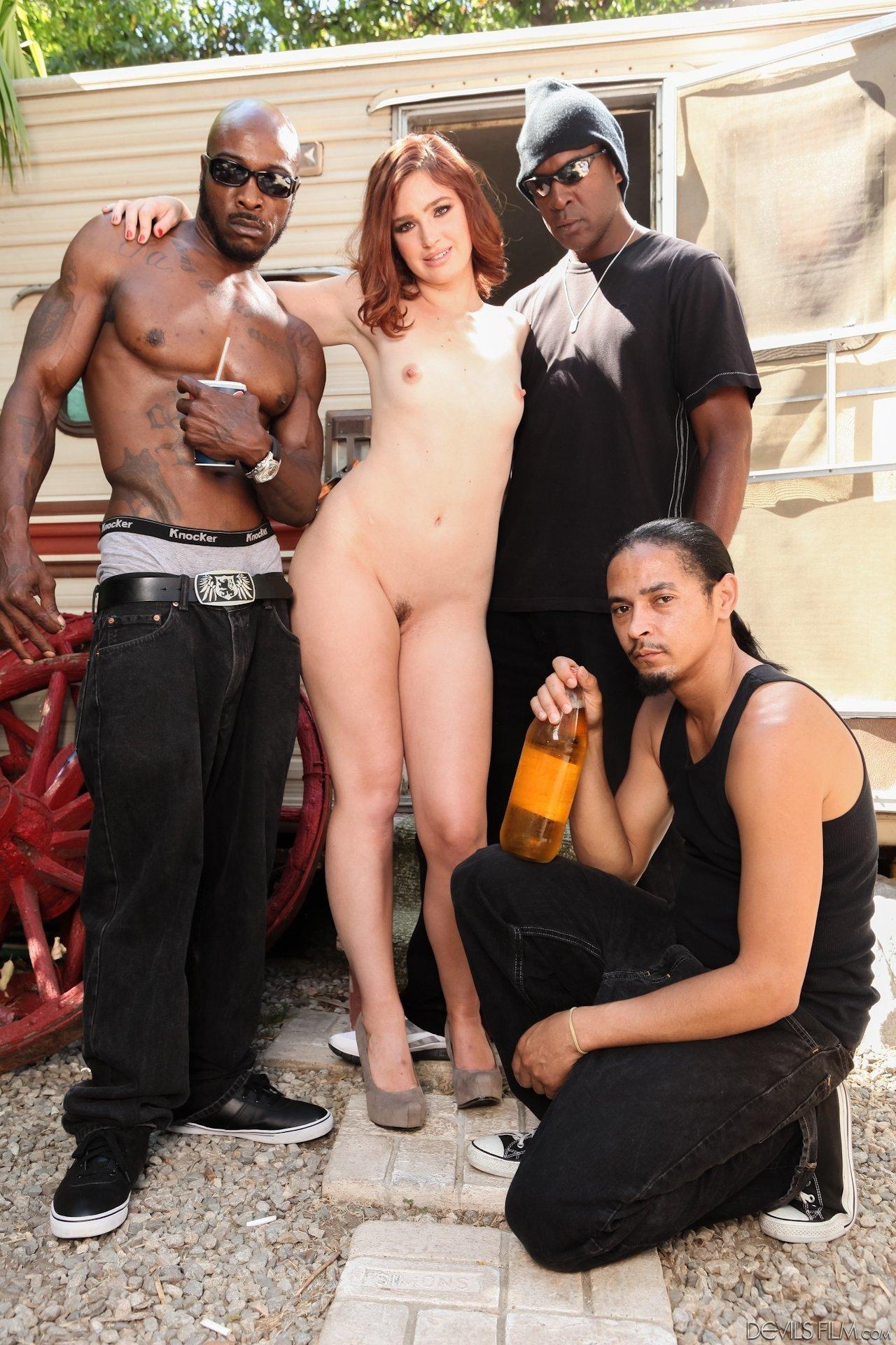 Рыжеволосая стройняшка фотографируется с тремя темнокожими мужчинами и можно только догадаться об их желаниях