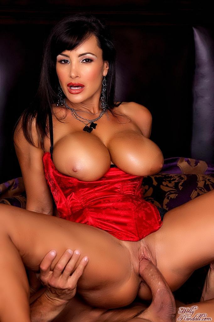 Похотливая милфа Lisa Ann в красном корсете показывает свою громадную грудь и трахает свою подстриженную письку