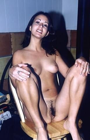 Чувственная и блистательная брюнетка сидит на табуретке и показывает лохматую писю