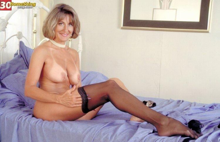 Грудастая возбуждающая дамочка надела чулки на ножки и подготовилась к сексу